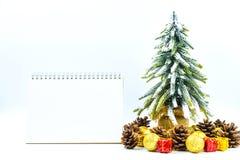 Fondo de la Navidad o del Año Nuevo con el cuaderno de notas en blanco, conos del pino, Fotos de archivo libres de regalías