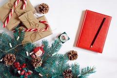 Fondo de la Navidad o del Año Nuevo: piel-árbol, ramas, regalos, decoración, cuaderno rojo con la pluma en un fondo blanco Fotografía de archivo libre de regalías
