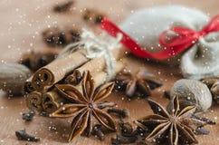 Fondo de la Navidad para la postal de Navidad Palillos de canela, estrellas del anís y clavos en fondo de madera Nieve exhausta Imágenes de archivo libres de regalías