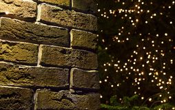 Fondo de la Navidad de la pared de ladrillo con brillar intensamente de las luces Fotografía de archivo libre de regalías