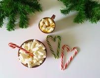 Fondo de la Navidad, tarjeta de felicitación con una taza de café o chocolate con las melcochas, las piruletas, una placa roja y  libre illustration
