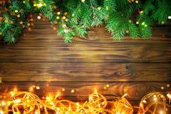 Fondo de la Navidad, una tabla adornada con las ramas de la guirnalda y del abeto de la Navidad con Año Nuevo y la Navidad Imagen de archivo
