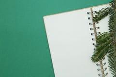 Fondo de la Navidad verde o del Año Nuevo con un cuaderno en blanco y una rama spruce Foto de archivo