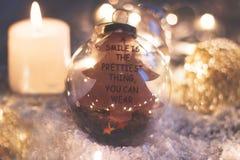 Fondo de la Navidad y del Año Nuevo - la bola de cristal con el ` de la cita una sonrisa es el ligh más bonito de la cosa que ust Imágenes de archivo libres de regalías