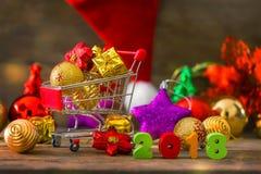 Fondo de la Navidad y del Año Nuevo con el carro de la compra miniatura w Imagenes de archivo