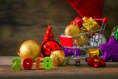 Fondo de la Navidad y del Año Nuevo con el carro de la compra miniatura w Fotografía de archivo