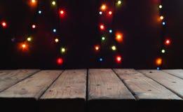 Fondo de la Navidad y del Año Nuevo con la tabla de madera oscura en blanco en un fondo de las luces del bokeh Foto de archivo libre de regalías