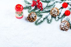 Fondo de la Navidad y del Año Nuevo con la vela de la Navidad y las ramas de árbol de navidad Imagen de archivo