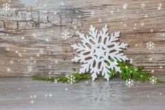 Fondo de la Navidad y del Año Nuevo El copo de nieve blanco grande en una tabla gris con un verde ramifica con la reflexión Fotos de archivo libres de regalías