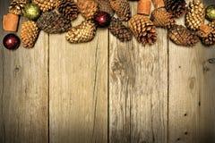 Fondo de la Navidad y frontera de madera del cono del pino Foto de archivo libre de regalías
