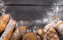 Fondo de la panadería del pan Brown y composición blanca de los panes del grano del trigo Fotos de archivo