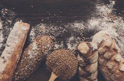 Fondo de la panadería del pan Brown y composición blanca de los panes del grano del trigo Imagen de archivo