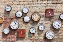Fondo de la pared de ladrillo con numeroso alrededor y los relojes cuadrados fotos de archivo libres de regalías