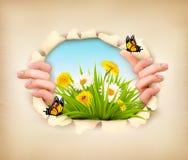 Fondo de la primavera con las manos, rasgando el papel para mostrar un paisaje Imagen de archivo libre de regalías