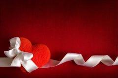 Fondo de la tarjeta del día de San Valentín - corazón rojo con el arqueamiento Fotos de archivo libres de regalías