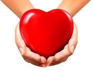 Fondo de la tarjeta del día de San Valentín del día de fiesta con las manos que llevan a cabo el corazón rojo Imagenes de archivo