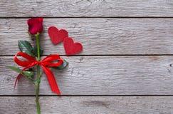Fondo de la tarjeta del día de San Valentín con la flor de la rosa del rojo, corazones de papel en la madera rústica Fotografía de archivo libre de regalías