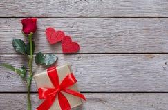 Fondo de la tarjeta del día de San Valentín con la flor de la rosa del rojo, los corazones de papel y la actual caja en la madera Fotografía de archivo libre de regalías