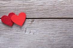 Fondo de la tarjeta del día de San Valentín con los corazones hechos a mano en la madera rústica Fotografía de archivo