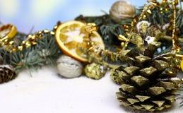 Fondo de la tarjeta del ` s del Año Nuevo con el cono del pino del abeto del oro de la Navidad Foto de archivo