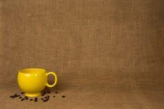 Fondo de la taza de café - taza y habas amarillas Fotos de archivo libres de regalías