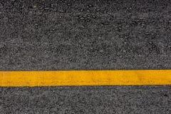 Fondo de la textura de la carretera de asfalto con las rayas amarillas Imagen de archivo libre de regalías