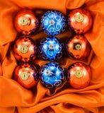 Fondo de las bolas anaranjadas y azules del árbol de navidad en tela de seda anaranjada Fotos de archivo