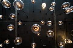 Fondo de las bombillas sobre la pared oscura imagen de archivo libre de regalías