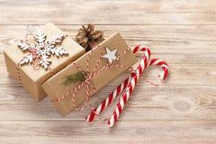 Fondo de las decoraciones de la Navidad o del Año Nuevo con los conos del pino, las cajas de regalo y el caramelo en el fondo bla Fotografía de archivo libre de regalías