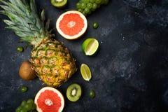 Fondo de las frutas tropicales Pi?a, pomelo, kiwi, uvas, cal en un fondo oscuro Verano, salud, vitaminas, vegano imagenes de archivo