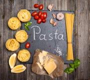 Fondo de las pastas con los ingredientes para cocinar en tablero de la pizarra, a Foto de archivo