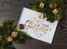 Fondo de las ramas y del espacio de árbol para los saludos con Feliz Navidad del texto Letras de la caligrafía Fotografía de archivo