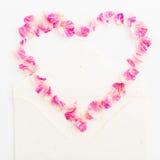 Fondo de las tarjetas del día de San Valentín Símbolo del corazón Pétalos de rosas y de tarjetas de papel del vintage en el fondo Imágenes de archivo libres de regalías