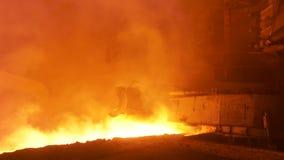 Fondo de las trabajos de metalistería con el acero fundido que fluye en el canal inclinado Cantidad común Equipo metalúrgico y te almacen de video
