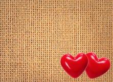 Fondo de lino de la textura con dos corazones rojos Fotografía de archivo