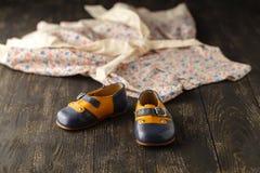 Fondo de los accesorios del bebé: vestido y zapatos ligeros de la flor para los vagos Imágenes de archivo libres de regalías