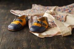 Fondo de los accesorios del bebé: vestido y zapatos ligeros de la flor para los vagos Imagenes de archivo