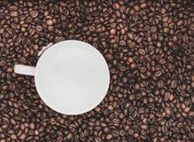 Fondo de los granos de café con la taza blanca Foto de archivo libre de regalías