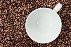 Fondo de los granos de café con la taza vacía del café con leche Foto de archivo