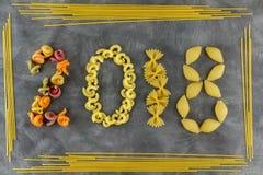 Fondo de los ingredientes alimentarios Tema del Año Nuevo Diversas clases de pastas Macarrones del trigo integral, espagueti, tal Imagen de archivo libre de regalías