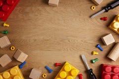 Fondo de los juguetes de los niños Herramientas coloridas del juguete, bloques de la construcción y tabla de madera del cubeson V foto de archivo libre de regalías