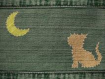 Fondo de los pantalones vaqueros con la figura de un gato Imagen de archivo libre de regalías