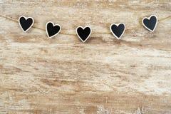 Fondo de madera acogedor, con 5 corazones negros sujetados entre ellos con una cuerda del cáñamo, concepto del amor, para el día  fotografía de archivo libre de regalías