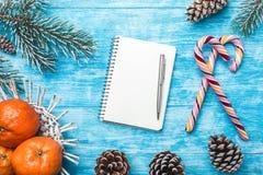 Fondo de madera azul Árbol de abeto verde Caramelos coloridos Fruta con el mandarín Tarjeta de felicitación de la Navidad y Año N Fotos de archivo libres de regalías