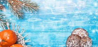 Fondo de madera azul Árbol de abeto verde Conos decorativos Dulces Fruta con el mandarín Espacio para el mensaje de la Navidad o  Foto de archivo
