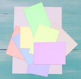Fondo de madera azul y papeles mezclados vacíos, coloridos Foto de archivo