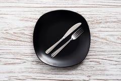 Fondo de madera blanco de la tabla de la placa de la bifurcación de los cubiertos vacíos del cuchillo Fotografía de archivo