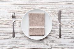 Fondo de madera blanco de la tabla de la placa de la servilleta de la bifurcación de los cubiertos vacíos del cuchillo Imagen de archivo