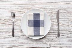 Fondo de madera blanco de la tabla de la placa de la servilleta de la bifurcación de los cubiertos vacíos del cuchillo Fotos de archivo