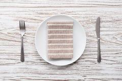 Fondo de madera blanco de la tabla de la placa de la servilleta de la bifurcación de los cubiertos vacíos del cuchillo Fotos de archivo libres de regalías